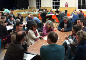 people discussing around tables at community workshop